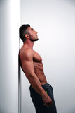 Muscular man leaning against the wall a Stock Photos