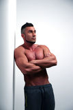 Muscular man leaning on the wall Stock Image