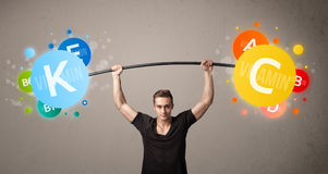 Muscular man lifting colorful vitamin weights Stock Photography