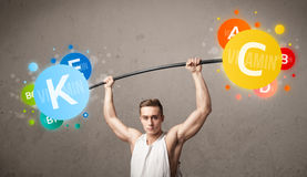 Muscular man lifting colorful vitamin weights Royalty Free Stock Photos