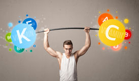 Muscular man lifting colorful vitamin weights Royalty Free Stock Photography