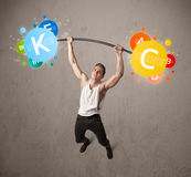 Muscular man lifting colorful vitamin weights Stock Photos