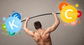 Muscular man lifting colorful vitamin weights Stock Photos
