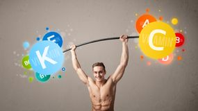 Muscular man lifting colorful vitamin weights. Strong muscular man lifting colorful vitamin weights royalty free stock images