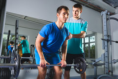 Muscular Man Lifting Deadlift In The Gym with instructor Stock Photography
