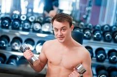 Muscular man lifting dumbbell Royalty Free Stock Photos