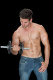 Muscular man lifting dumbbell in blue jeans Stock Photos