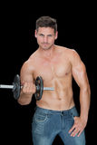 Muscular man lifting dumbbell in blue jeans Royalty Free Stock Photo