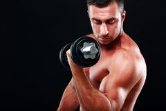 Muscular man lifting dumbbell Royalty Free Stock Images