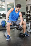 Muscular man lifting dumbbell while sitting on bench Royalty Free Stock Photography