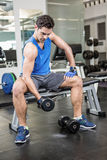 Muscular man lifting dumbbell while sitting on bench Stock Photography