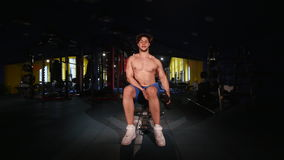 Muscular man lifting dumbbell in sport club.  stock video