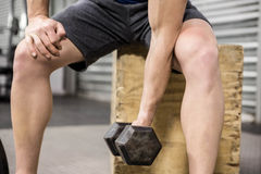 Muscular man lifting dumbbell on wooden block Stock Photos