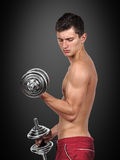 Muscular man lifting dumbbells Royalty Free Stock Images