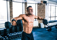 Muscular man lifting dumbbells Stock Photography
