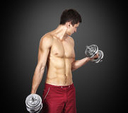Muscular man lifting dumbbells Stock Images