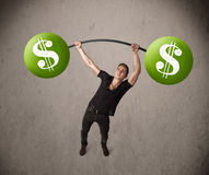Muscular man lifting green dollar sign weights Royalty Free Stock Photography