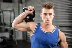 Muscular man lifting heavy kettlebell Stock Photo
