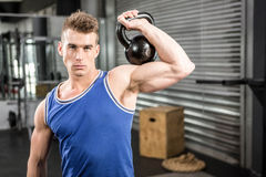 Muscular man lifting heavy kettlebell royalty free stock image