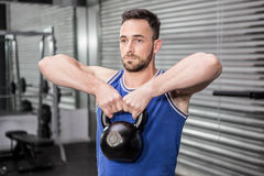 Muscular man lifting heavy kettlebell stock photos