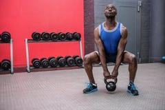 Muscular man lifting a kettlebell Stock Images