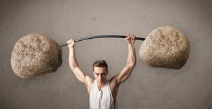 Muscular man lifting large rock stone weights. Strong muscular man lifting large rock stone weights stock images