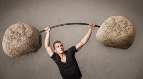 Muscular man lifting large rock stone weights. Strong muscular man lifting large rock stone weights royalty free stock images