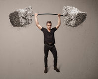 Muscular man lifting large rock stone weights Stock Photography