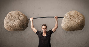 Muscular man lifting large rock stone weights Royalty Free Stock Photography
