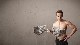 Muscular man lifting large rock stone weights Royalty Free Stock Image