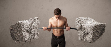 Muscular man lifting large rock stone weights Royalty Free Stock Photos