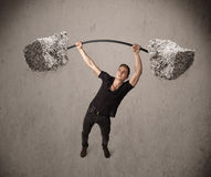 Muscular man lifting large rock stone weights Stock Image