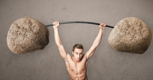 Muscular man lifting large rock stone weights Stock Images