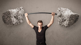 Muscular man lifting large rock stone weights Royalty Free Stock Photos