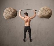 Muscular man lifting large rock stone weights Stock Photos