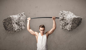 Muscular man lifting large rock stone weights Stock Photos