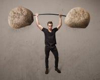 Muscular man lifting large rock stone weights Stock Photo