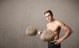 Muscular man lifting large rock stone weights Royalty Free Stock Images