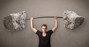 Muscular man lifting large rock stone weights Stock Photo