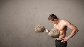 Muscular man lifting large rock stone weights Stock Image