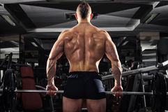 Muscular Man Lifting Some Heavy Barbells. Athlete Working Out. Full Back View Stock Photos
