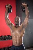 Muscular man lifting two kettlebells Stock Photography