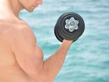 Muscular man lifting weight Stock Photos