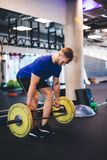 Muscular man lifting weights at the gym. Strong body, exercising and sport stock photos
