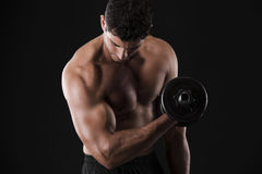 Muscular man lifting weights. Portrait of a muscular man lifting weights against a dark background stock images