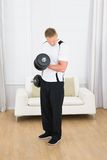 Muscular man lifting weights. Portrait Of A Muscular Man Lifting Weights At Home Stock Images