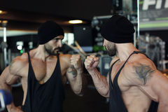 Muscular man looking in mirror himself Stock Image