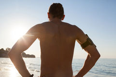 Muscular man looking at sea from beach Stock Photo