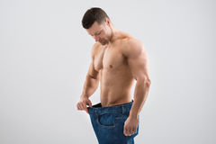 Muscular Man Looking At Weight Loss While Holding Old Jeans. Mid adult muscular man looking at weight loss while holding old jeans against white background Stock Image