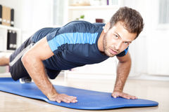 Muscular Man Looking at You While Doing Push ups Royalty Free Stock Image